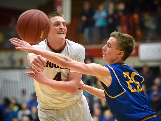 Rocori's Connor Schoborg passes around Logan Nagorski of Big Lake during the Thursday, March 16, Section 5-3A playoff game at Halenbeck Hall in St. Cloud.