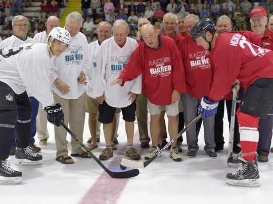 """Dustin Brown, left, and Joe Nieuwendyk take the ceremonial puck drop as members of the Cornell national-championship team of 1969-70 look on prior to the second annual """"Racker Rivals Big Red"""" benefit hockey game Saturday night at Lynah Rink. Dropping the puck is John Hughes, captain of the championship team. The '69-70 Big Red finished 29-0, and is the only men's team in NCAA Division I history to go through a season undefeated."""