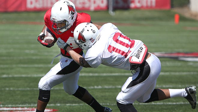 Ball State's Ralph Smith is grabbed during a scrimmage at Scheumann Stadium Saturday.