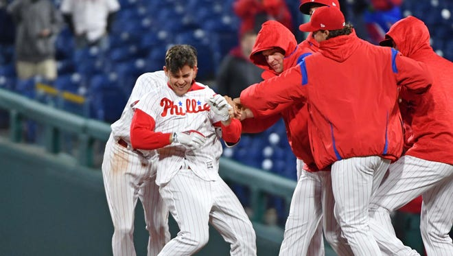 Philadelphia Phillies second baseman Scott Kingery (4) is mobbed by teammates after walk-off sacrifice fly in the 12th inning against the Cincinnati Reds at Citizens Bank Park.