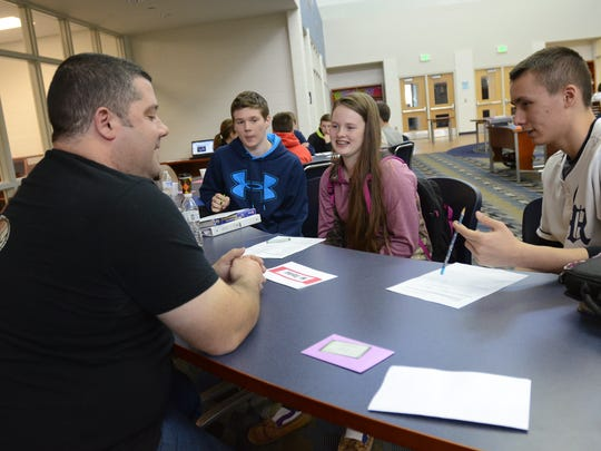 Economics class students ask Mike Taylor, left, questions about how to start a successful business Monday at Marysville High School.