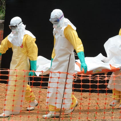 Staff of the 'Doctors without Borders' medical aid organisation carry the body of a person killed by viral haemorrhagic fever, at a center for victims of the Ebola virus in Guekedou, on April 1, 2014.