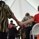 Guests held hands during a prayer portion of the ceremony dedicating the Muhammad Ali Childhood Home Sunday afternoon. May 2016.