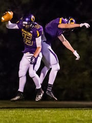 Oconomowoc senior Koty Thelen (15) celebrates a 54-yard touchdown with Jack Bourdo (3) in the second quarter against Wisconsin Lutheran on Friday, Sept. 27, 2013.