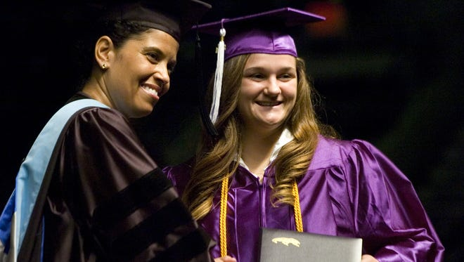 Cypress Lake High School Principal Tracy Perkins poses with a student during the 2011 commencement ceremony. Perkins issued her resignation on July 14, 2014