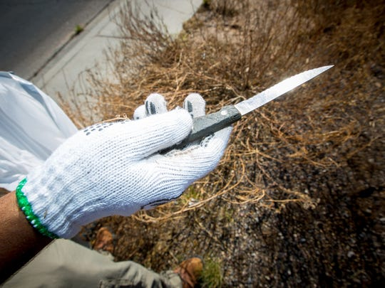 NMSU Junior, and ESSO member, Matthew Gonzales holds up a knife he found while picking up trash in an empty lot behind the Sonic Drive-In on Foothills Rd as part of the Great American Cleanup, April 9, 2016.