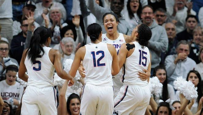 Connecticut's Napheesa Collier, center, reacts with teammates Crystal Dangerfield, left, Saniya Chong, and Gabby Williams, right, in the second half.