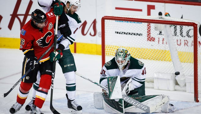 Minnesota Wild goalie Devan Dubnyk (40) deflects a shot as defenseman Marco Scandella (6) holds off Calgary Flames right wing Troy Brouwer (36) during the second period of an NHL hockey game Wednesday, Feb. 1, 2017, in Calgary, Alberta. (Jeff McIntosh/The Canadian Press via AP)