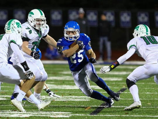 Catholic Central's Nicholas Capatina (with ball) slips