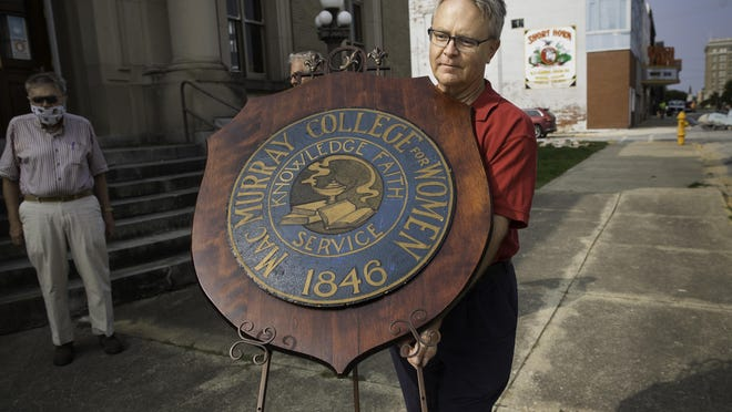 David Blanchette, chairman of the Jacksonville Area Museum, carries a large wooden plaque bearing the seal of MacMurray College outside the museum before a ceremony in front of the facility Thursday, Sept. 17, 2020. The MacMurray Foundation and the City of Jacksonville signed an agreement that places MacMurray College's artifact collection with the Jacksonville Area Museum, located at the old Post Office building on East State Street in Jacksonville, Ill. The museum will be responsible for preserving, curating and displaying the collection for the ten years. The museum will offer a limited look at the collection on Oct. 10 and plans an official opening in mid-2021.