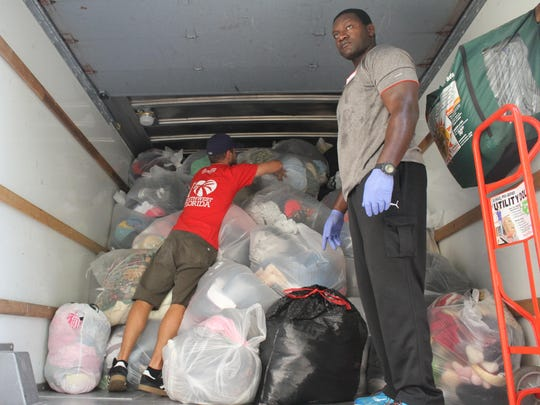 Volunteers Kevin Burkwit and Lemec Bernard load a U-Haul