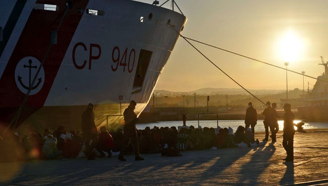 Shipwrecked migrants sit on the quayside after disembarking from a rescue vessel in the Italian port of Augusta in Sicily on April 16.