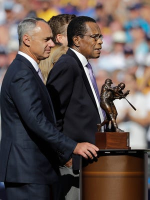 Former baseball player Rod Carew stands next to the batting title trophy named after him with baseball commissioner Rob Manfred prior to the MLB baseball All-Star Game, Tuesday, July 12, 2016, in San Diego. (AP Photo/Gregory Bull)