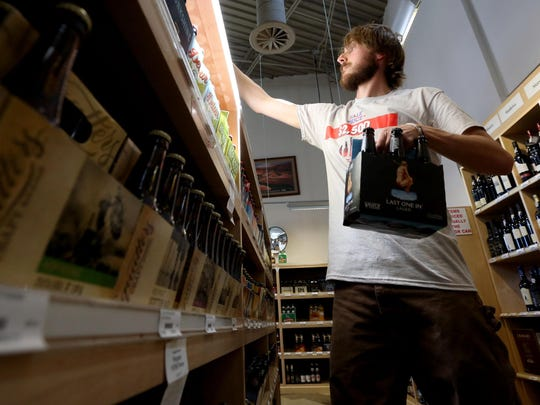 In this Thursday, July 2, 2015 photo, Glen Simister stocks beer at the Utah State Liquor Store in Holladay. State lawmakers approved Monday a one-week grace period for store owners to purchase and store 4% beer before it can be sold to customers as the cap is lifted from 3.2% beer.