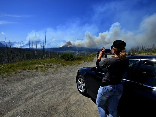 Stacey Westfahl, of Wichita, Kan., takes photos from a turnout on Highway 89 overlooking St. Mary Lake in Glacier National Park as the Reynolds Creek Fire continues to burn on the north side of the lake Wednesday afternoon.