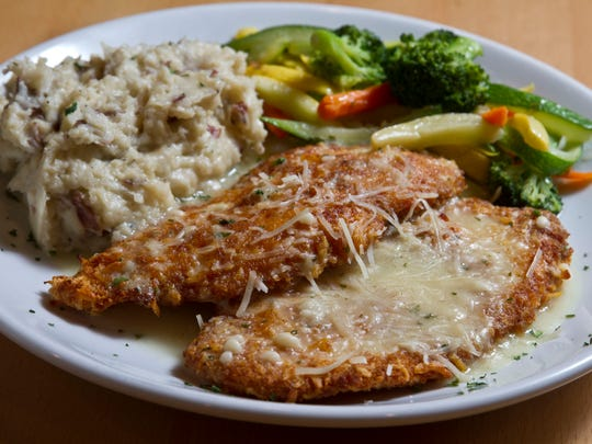 Parmesan-crusted chicken with garlic mashed potatoes and a vegetable medley at Lighthouse Tavern.