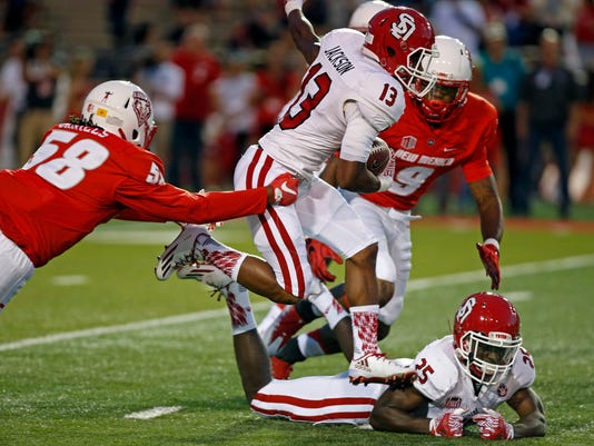 South Dakota wide receiver Shamar Jackson (13) carries past the defense of New Mexico linebacker Maurice Daniels (58) and defensive back Stanley Barnwell Jr. (9) during the first half of an NCAA college football game in Albuquerque, N.M., Thursday, Sept. 1, 2016. (AP Photo/Andres Leighton)
