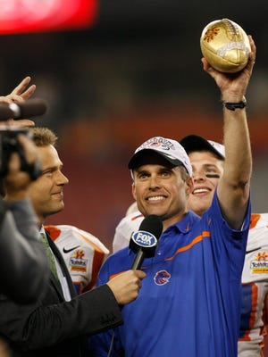 Boise State head coach, Chris Petersen hoists the Tostitos Fiesta Bowl Trophy after his Broncos defeated Oklahoma in overtime on Jan. 1, 2007.
