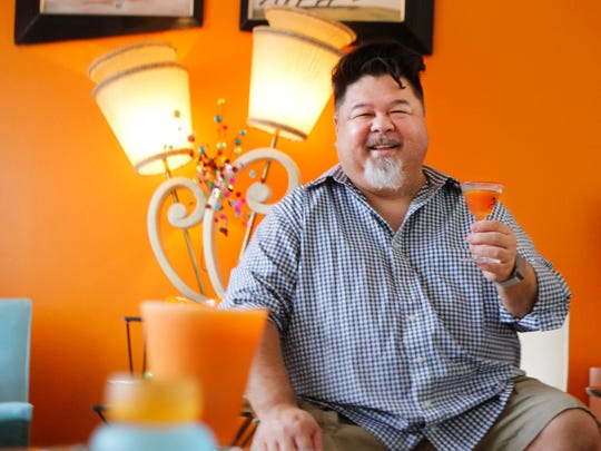 Chef John Castro holds a bourbon holiday drink in the living room of his home.