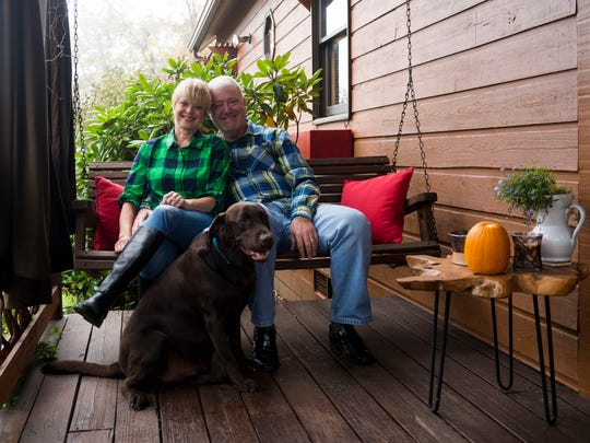 """Jenna Jefferson, husband Keith Ford and Muddy, their chocolate Lab, relax on the front porch swing. The swing's days may be numbered. Inspired by a visit to Greenville, South Carolina, Jenna says, """"I saw a hanging day bed and said to Keith, 'That's what you're going to build me next.' """""""
