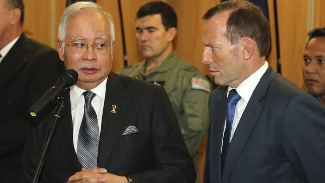 Australian Prime Minister Tony Abbott, right, speaks as Malaysia Prime Minister Najib Razak looks on during a breakfast with crewmembers from different countries involved in the search for the missing Malaysia Airlines Flight MH370 at Pearce Airbase.