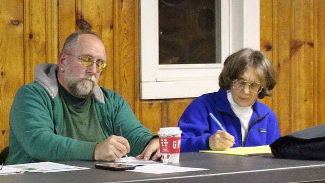 Panelists Bill Baker, a local environmental activist, and Deborah Fleming, a professor at Ashland University, take notes during a meeting on potential fracking in Hayesville on Monday, Dec. 11, 2017. The panelists encouraged residents to talk to their neighbors and get water well testing done.