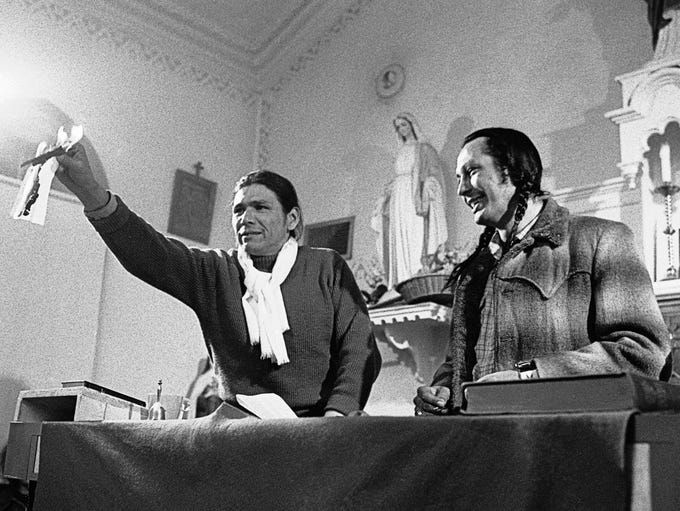 Dennis Banks, AIM official, holds burning paper on