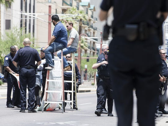 Two protesters chained themselves atop two ladders