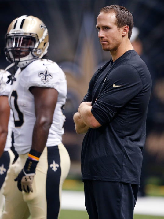 New Orleans Saints quarterback Drew Brees watches from the sideline in street clothes before an NFL football game against the Tennessee Titans in New Orleans, Friday, Aug. 15, 2014. (AP Photo/Bill Haber)
