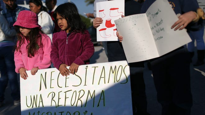 Katherine Diaz, left, and Nayleth Martinez stand with other demonstrators at the office of Sen. Marco Rubio, R-Fla., on Dec. 10, 2014 in Doral, Fla. The demonstrators called on Rubio to support President Obama's immigration initiatives.