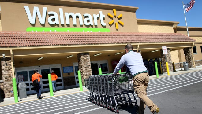 Walmart employee Yurdin Velazquez pushes grocery carts at a Walmart store on February 19, 2015 in Miami.