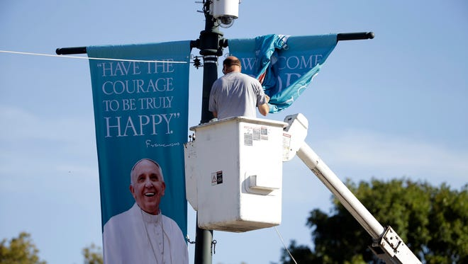A worker hangs banners ahead of Pope Francis' scheduled visit in Philadelphia.
