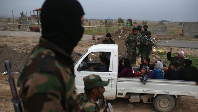 Kurdish Peshmerga soldiers watch as people flee an ISIL or, in Arabic, Daesh-held front line village on Monday to Sinjar, Iraq. Peshmerga forces carefully screened the displaced Iraqis as they arrived, fearing enemy infiltrators and suicide bombers. Kurdish forces, with the aid of massive U.S.-led coalition airstrikes, liberated Sinjar from ISIL extremists, moving the frontline south.