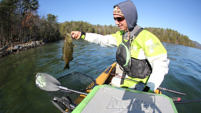 Spencer Cooke, director of the Jackson Kayak Triple Crown of Kayak Fishing Tournament, catches a smallmouth bass on Lake Jocassee last year.