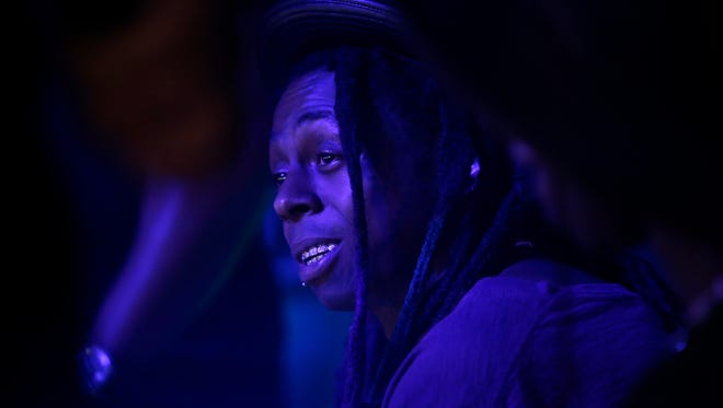 Lil Wayne sits on stage during his appearance at the Coliseum on Friday, March 20, 2015.