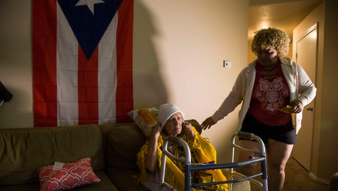 Grace Castro takes care of her grandmother Engracia Morales, 91, after they both fled hurricane-ravaged Puerto Rico for Castro's sister's home in Phoenix. Castro's 4-year-old son and her 63-year-old mother also left Puerto Rico for Phoenix.