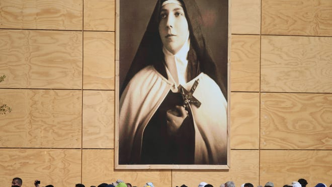 An image of Chilean Saint Teresa de los Angeles hangs over the crowd waiting for Pope Francis to arrive for Mass at O'Higgins Park in Santiago, Chile, Tuesday, Jan.16, 2018.