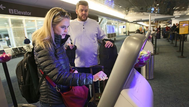 Lindsey Haischer and her husband Ben Haischer of Mequon use the kiosk to check in at the Southwest counter area at Milwaukee's Mitchell International Airport as they head out to Scottsdale, Ariz.