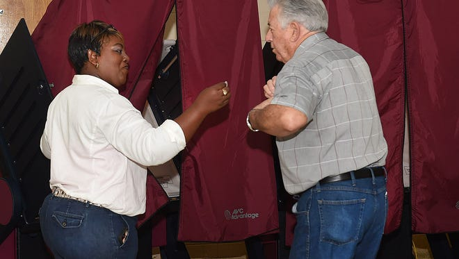 Nolton Brown enters the voting booth to cast his vote Tuesday morning.