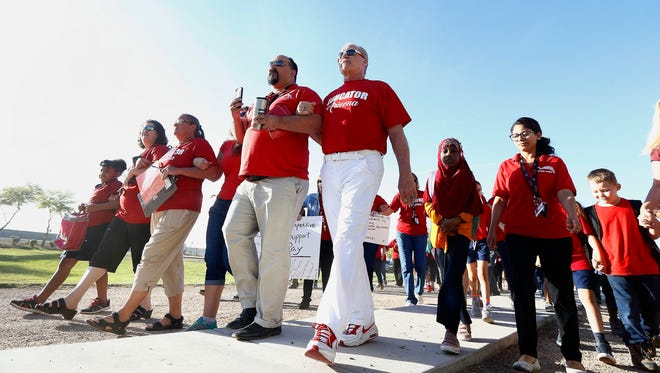 """Teachers at Tuscano Elementary School stage a """"walk-in"""" for higher pay and school funding as they walk into school on April 11, 2018, in Phoenix. Teachers gathered outside Arizona schools to show solidarity in their demand for higher salaries staging """"walk-ins"""" at approximately 1,000 schools that are part of a statewide campaign for a 20 percent raise and more than $1 billion in new education funding."""