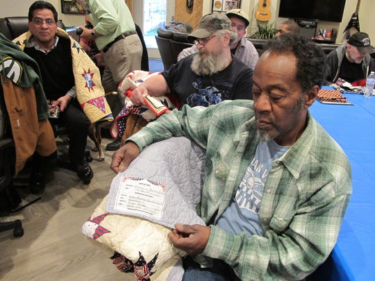 Richard Butler, a Marine who served in Vietnam, looks at the label on his new quilt to see the names of the quilters who made it. Butler was one of 15 homeless veterans at the James A. Peterson Veterans Village in Racine who received quilts from Quilts of Valor.