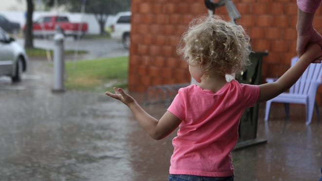 A little girl holds out her hand to catch drops of rain as her and her family take cover under the awning sign in front of the San Angelo Museum of Fine Arts during Family Day STEAM Saturday, Aug. 13, 2016. Michelle Gaitan/Standard-Times