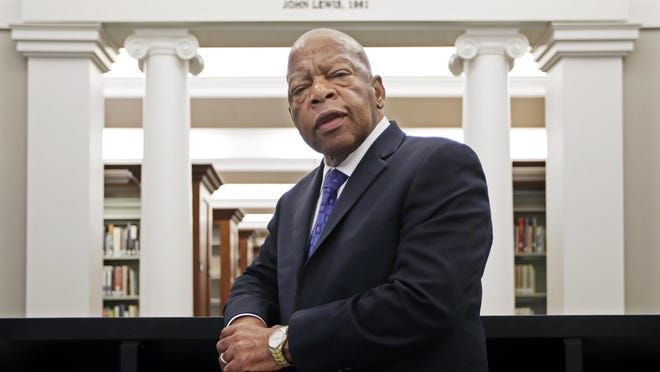 FILE - In this Nov. 18, 2016, file photo, U.S. Rep. John Lewis, D-Ga., poses for a photograph under a quote of his that is displayed in the Civil Rights Room in the Nashville Public Library in Nashville, Tenn. Lewis announced Sunday, Dec. 29, 2019, that he has stage IV pancreatic cancer, vowing he will stay in office and fight the disease with the tenacity which he fought racial discrimination and other inequalities since the civil rights era.