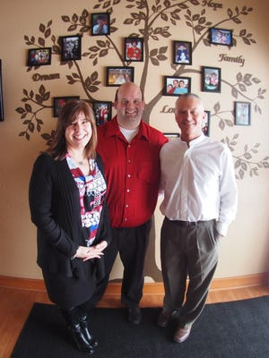 Pictured, from left, are Leslie Jaber-Wilson, Damian Lonnee and Kevin Wilson, the trio behind Pillar & Vine, a private foster care agency. Behind them are photos of their families, which were brought together through fostering and adoption.