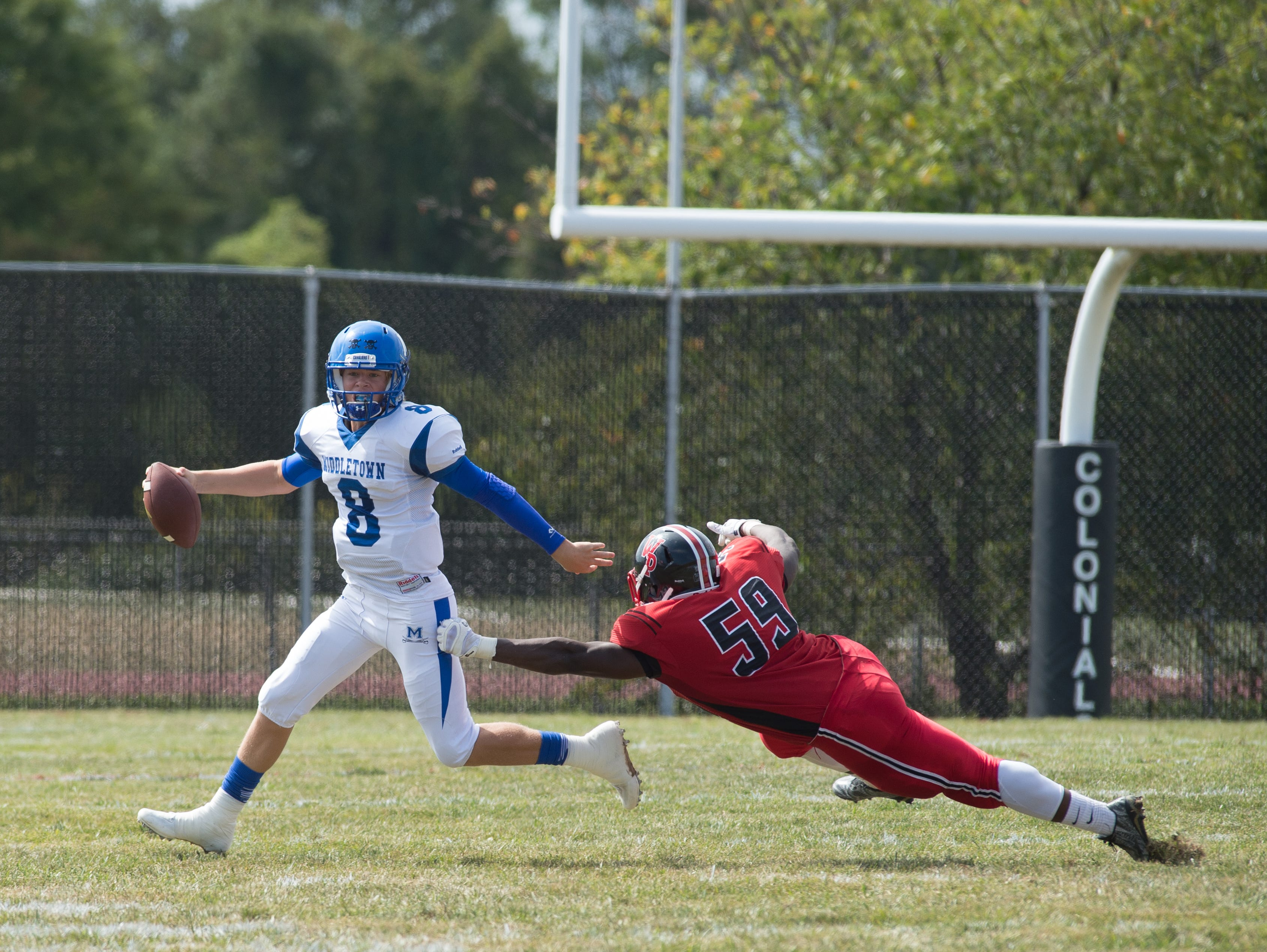 Middletown's quarterback Drew Fry (8) escapes a tackle from William Penn's Collins Adu-Gyamfi (59).