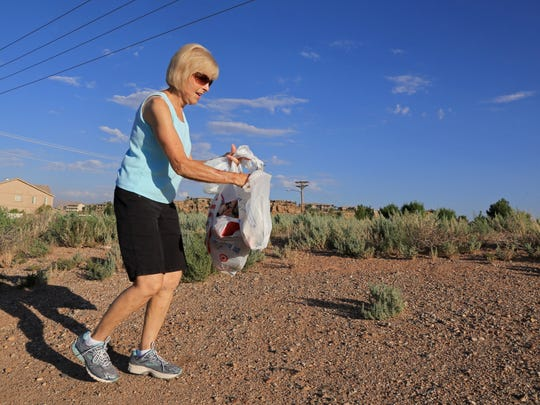 Linda Goduto picks up litter Tuesday morning on the corner of 2450 East and River Road in St. George.