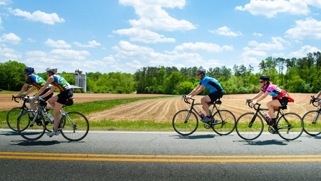 Cyclists pass a farm during the Cycle to Farm bike tour last year, which takes riders on a 62-mile tour to visit several Western North Carolina farms. The fourth annual Cycle to Farm is July 18.