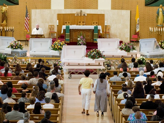 Monsignor Richard O'Keeffe leads mourners in the rosary