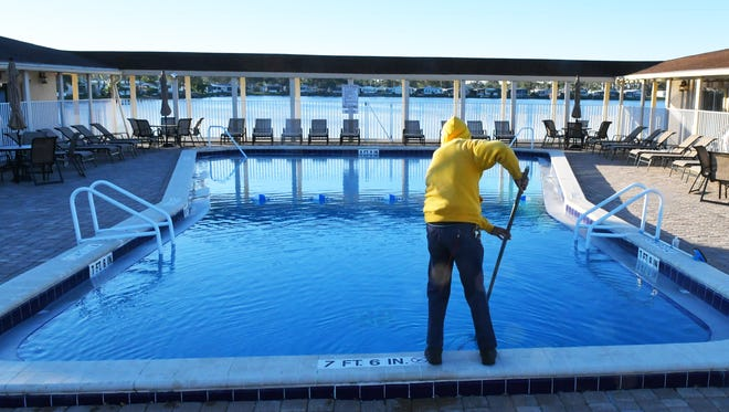 On a cold Monday morning, Joe Moramarco performs the daily cleaning of the heated pool at Lamplighter Village, a 55 plus community in Melbourne. Joe says that, despite the cold, there were a couple of swimmers on Sunday.