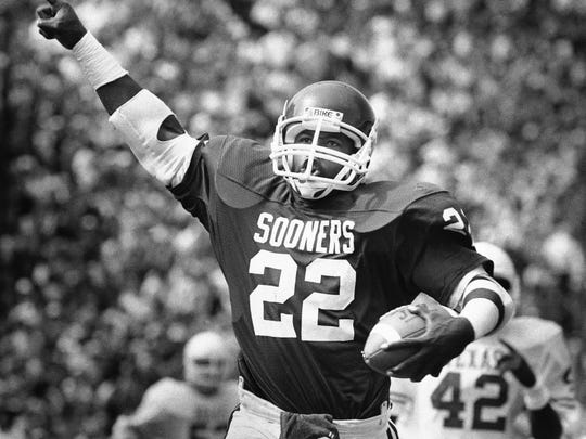 Oklahoma halfback Marcus Dupree hoists a sign of victory